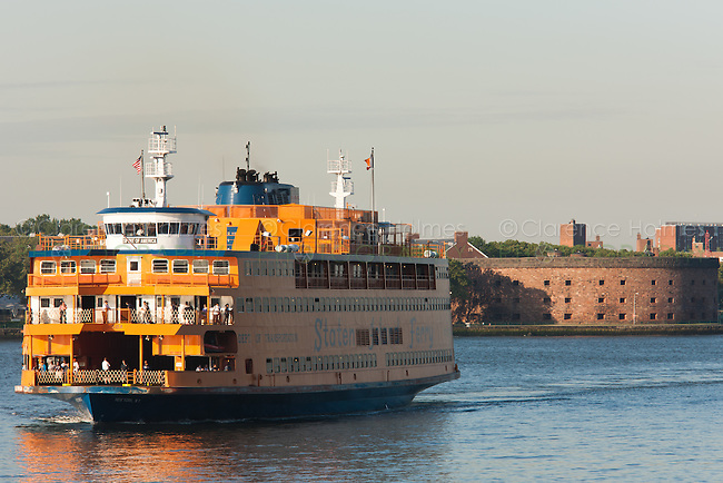Staten Island Ferry Spirit of America approaches the Whitehall Ferry Terminal in Manhattan, New York City.  Castle Williams on Governors Island is in the background.