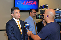 4 May 2012:  FIU Executive Director of Sports and Entertainment Pete Garcia (at podium) is interviewed by media following a press conference during which the FIU Golden Panthers, currently a member of the Sun Belt Conference, formally announced their acceptance of an invitation to join Conference USA for all sports starting July 1, 2013, at the FIU Stadium Club in Miami, Florida.