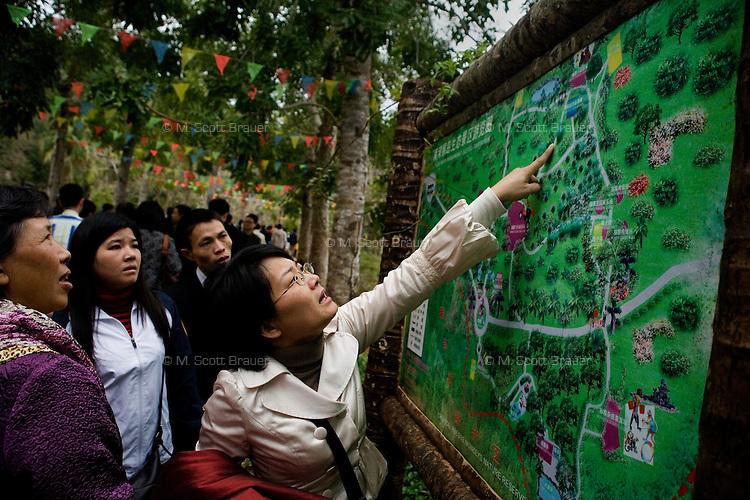 Visitors look at a map of Monkey Island near Lingshui, Hainan, China.