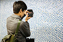 "A man takes a photograph of a wall of 100,000 Slime characters in Shinjuku Station on February 26, 2015. 100,000 Blue Slime from the game of Dragon Quest are displayed in bubble-wrap in a corridor of Shinjuku Station. The wall was created to promote the newest video game ""Dragon Quest Heroes: The Dark Dragon and the World Tree Castle"" for Playstation 3 and 4. Passersby can pop the Slimes and the goal of for all 100,000 bubbles to have been burst by the end of the campaign. There are special characters such as metal Slimes and Rockbombs hidden along the wall and the installation is accompanied by background music from the game. The promotion runs from February 23rd to March 1st in Tokyo. (Photo by Rodrigo Reyes Marin/AFLO)"