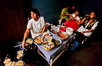 Mexican woman making tortillas for a group of girls  in an eatery
