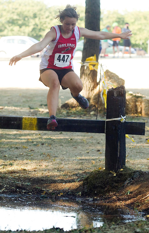 Kyzlen Stein of White Salmon High School jumps through some water as she runs in the women's varsity cross country race at Hudson's Bay High School's Run-A-Ree in Vancouver Friday September 12, 2014. ( Natalie Behring/for the Columbian)