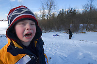 A youngster with cold fingers cries as his mother and sister enjoy sledding at Hoover Reservoir.