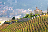 The Hermitage chapel on top of the hill with a view across the river on Tournon. The Hermitage vineyards on the hill behind the city Tain-l'Hermitage, on the steep sloping hill, stone terraced. Sometimes spelled Ermitage. The Tournon chateau and tower in the background Tain l'Hermitage, Drome, Drôme, France, Europe
