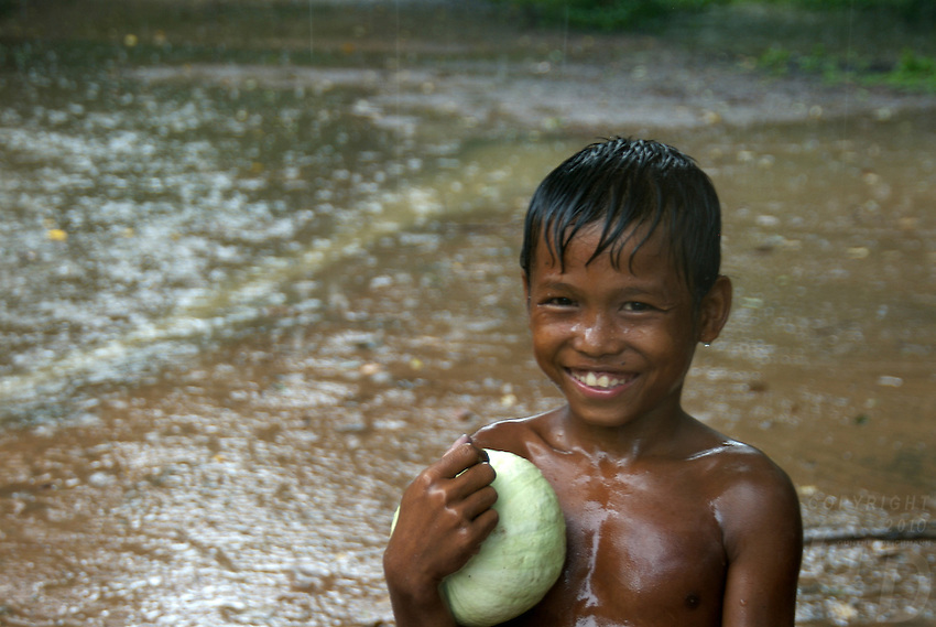 A very happy young boy during a heavy tropical Monsoon rain shower at Beng Mealea, Angkor area, Cambodia