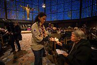 """Friedenslicht von Bethlehem kommt als Zeichen gegen Terror und Gewalt nach Berlin.<br /> Die Kaiser-Wilhelm-Gedaechtnis-Kirchengemeinde empfing am dritten Adventssonntag das Friedenslicht von Bethlehem. Mehr als 500 Pfadfinderinnen und Pfadfinder brachten das Licht in die Kirche, wo es mit einem oekumenischen Gottesdienst empfangen wurde. Die Gedaechtniskirche wurde von den Pfadfinderverbaenden als Ort fuer die Uebergabe des Lichtes ausgewaehlt, um kurz vor dem Jahrestag des Anschlags auf dem Breitscheidplatz ein Zeichen gegen Terror und Gewalt zu setzen. <br /> Das Licht wird bei den Gedenkandachten und -veranstaltungen am 19. Dezember 2017, dem Jahrestag des Anschlags, als Quelle aller Kerzenflammen, z.B. auch bei der Lichterkette am Abend dienen.<br /> Das Friedenslicht ist eine Initiative des Oesterreichischen Rundfunks (ORF). Es wird seit 1986 in der Geburtsgrotte Jesu in Bethlehem von einem Kind entzuendet und nach Wien gebracht. Als Symbol fuer den Wunsch nach Frieden und der Sehnsucht nach einer gerechten und solidarischen Welt tragen Pfadfinderinnen und Pfadfinder das Licht am dritten Advent in ihre Heimatlaender. In Deutschland steht die diesjaehrige Friedenslichtaktion unter dem Motto: """"Auf dem Weg zum Frieden"""".<br /> In der Kaiser-Wilhelm-Gedaechtnis-Kirche wird das Friedenslicht bis zum Ende der Weihnachtszeit in einer Leuchte an einem zentralen Ort brennen. An der Flamme kann jeder eine Kerze entzuenden und das Licht auf diese Weise an andere Menschen weitergeben – beispielsweise in Kirchengemeinden oder Schulen.<br /> Im Bild: Pfadfinderinnen haben ihre Kerzen am Friedenslicht entzuendet und geben das Licht an die Gottesdienstteilnehmer weiter.<br /> 17.12.2017, Berlin<br /> Copyright: Christian-Ditsch.de<br /> [Inhaltsveraendernde Manipulation des Fotos nur nach ausdruecklicher Genehmigung des Fotografen. Vereinbarungen ueber Abtretung von Persoenlichkeitsrechten/Model Release der abgebildeten Person/Personen liegen nicht vor. NO MODEL RELEASE! Nur f"""