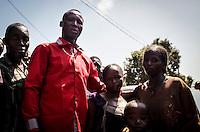 Anti-Balaka-Aktivist Emotion (rotes Hemd) bei der Übergabe von drei muslimischen Geiseln im Kindesalter (rechts) in Bangui, Zentralafrikanische Republik. ) bei der Übergabe von drei muslimischen Geiseln im Kindesalter (rechts) in Bangui, Zentralafrikanische Republik. Der Junge (Vordergrund) wurde bei der Flucht vor den Anti-Balaka-Milizen verletzt. Nach Angaben von Emotion fiel er und verletzte sich am linken Auge