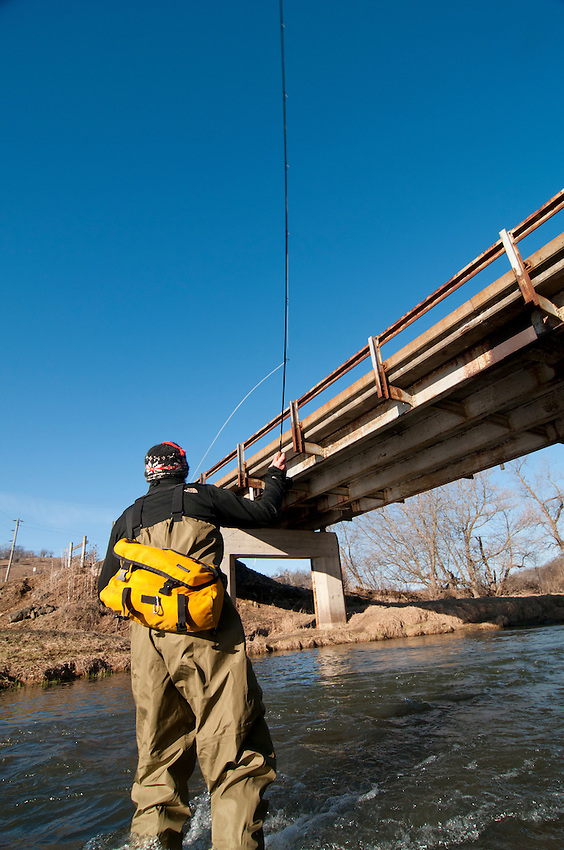 An angler casts near a bridge while fly fishing in the Driftless Area of southwest Wisconsin.