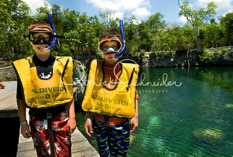 Two young boys prepare to snorkel in a lagoon of aqua water near Cancun, Mexico.