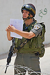 An Israeli border police officer holds up a document to approaching Palestinian, Israeli & International activists designating the area a closed military zone during a non-violent demonstration against Israel's controversial separation barrier in the West Bank town of Beit Jala, near Bethlehem on 11/07/2010.