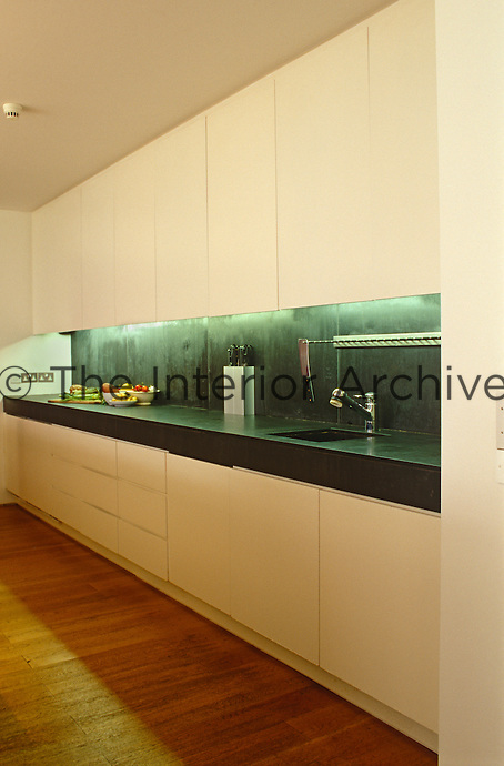 View down the length of the built-in kitchen unit and work surface along one wall of the open-plan kitchen