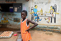 BURKINA FASO, Province Poni, Gaoua, wall painting as advertisement for beer bar, man and woman sitting at table drinking Brakina Beer, the local beer of the brewery in Burkina Faso, girl selling chicken eggs, slogan I love you and God is one