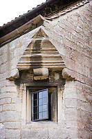 A small mullion window on the upper storey is set under a gable end in the stone wall