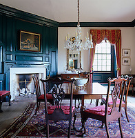 A formal dining room is partially decorated with blue-painted panelling