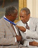 Bill Cosby admires Hank Aaron's Presidential Medal of Freedom which was awarded by United States President George W. Bush during a ceremony in the East Room of the White House in Washington, D.C. on July 9, 2002..Credit: Ron Sachs / CNP