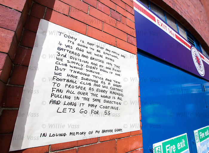 A Rangers fan writes a statement and puts it on the brickwork at Ibrox Stadium to mark the return of the club to the top flight after four years in the lower leagues