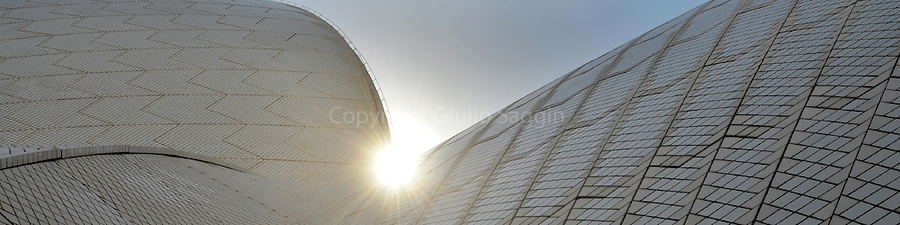 The sun's rays shine between two of the sails of the Sydney Opera House.
