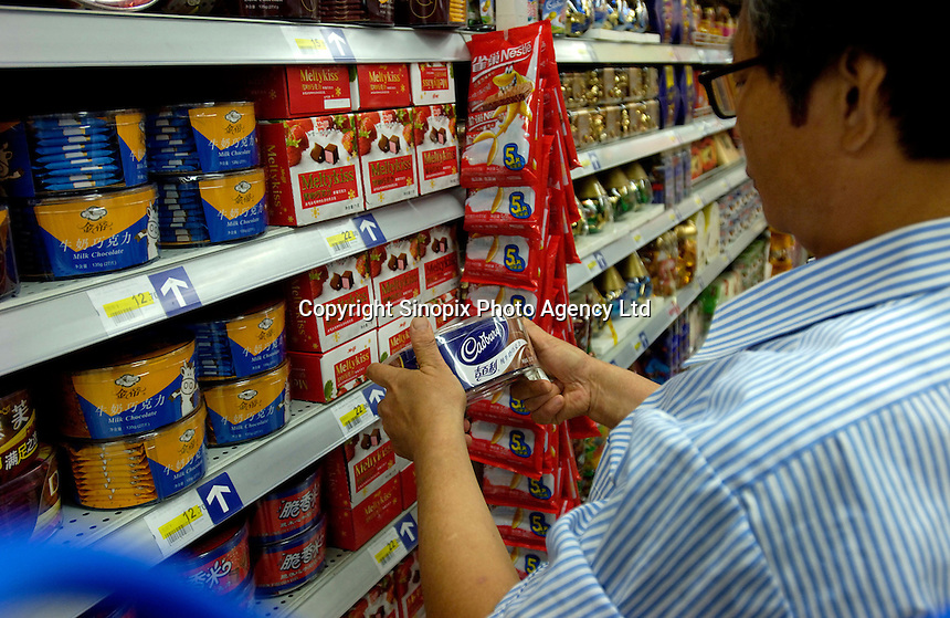 A man looks carefully at a box of Cadbury chocolates in a Carrefour supermarket in Beijing, China. Major international chains like Carrefour and Walmart Stores have expanded aggressively in China. Local Chinese retailers have loudly protested this and lobbied heavily for protection from the new competition in price and service that these major retailers have set off..22 Jul 2006