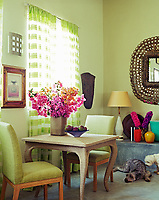 In this living room a rope-covered side table is arranged with two pistachio green linen-covered chairs in a pleasing contrast of colour and texture