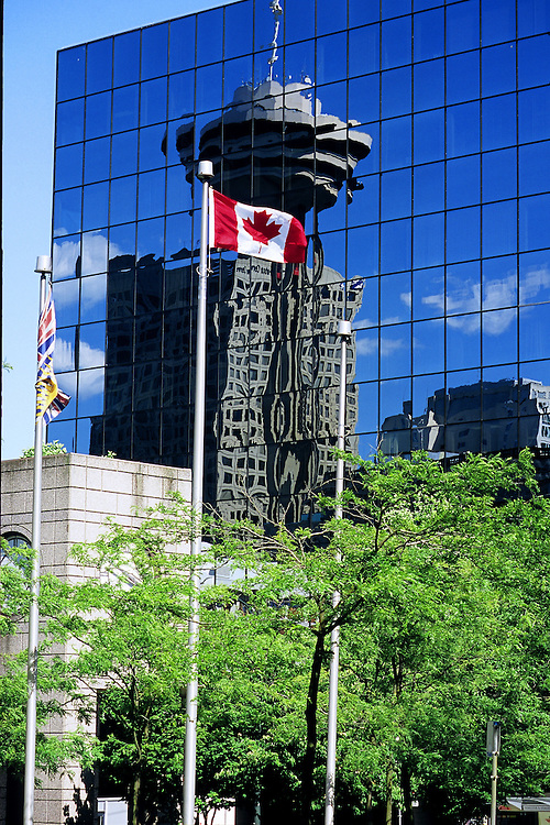Reflection of Harbor Center and revolving restaurant, with Canadian Maple Leaf flag in foreground, Vancouver, BC.
