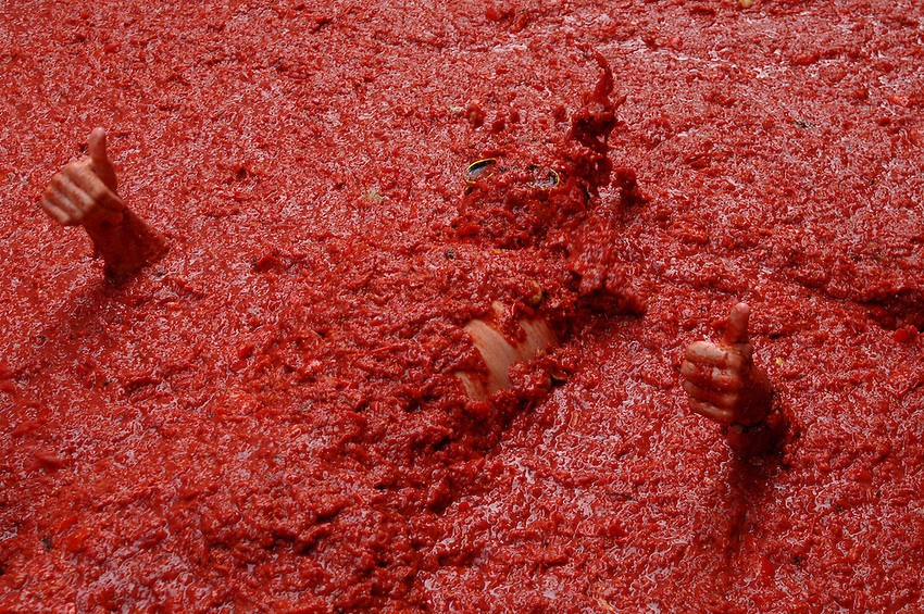 BUNYOL, SPAIN - AUGUST 31: A person immersed in tomato juice in the Tomatina August 31, 2005 in Bunyol, Valencia, Spain. Approximately 45,000 people pelted each other with a little over 100.000 kilograms of tomatoes. The tomatina is known as the world's largest tomato battle. Photo by Ander Gillenea