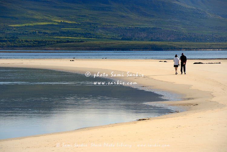 Couple walking in the morning by Flamingo lake estuary near Hermanus, South Western Cape, South Africa
