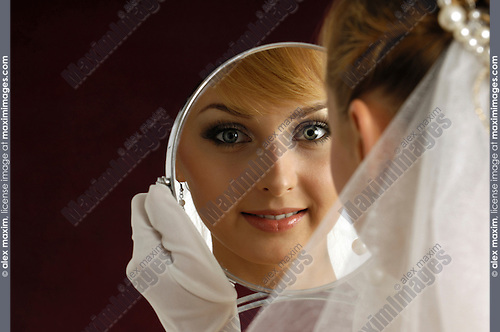 Stock photo of a Young beautiful smiling bride wearing a white wedding dress and a veil admiring herself in a looking-glass artistic conceptual portrait Twenty year old caucasian woman Isolated on dark red background