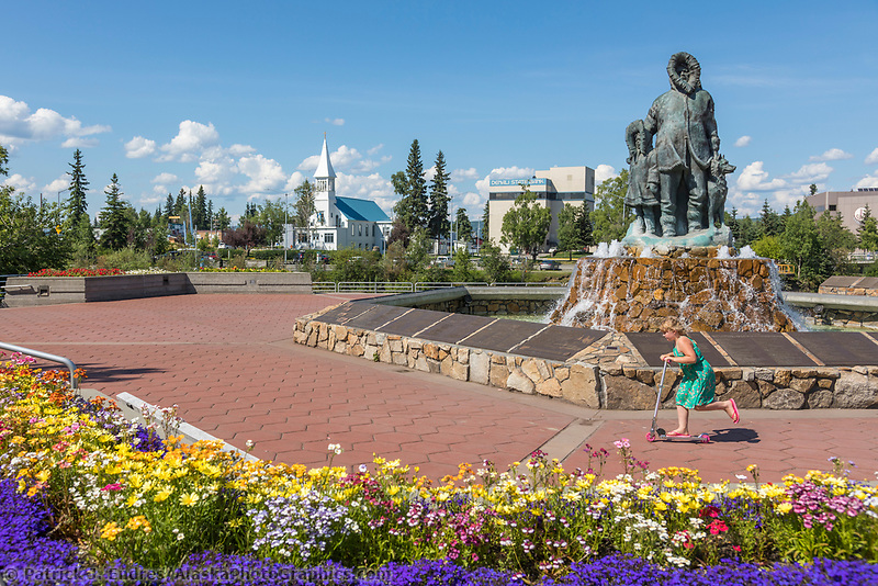 Tourist enjoys a sunny summer day in the Golden Heart Plaza by the First Family Statue in Downtown Fairbanks, Alaska