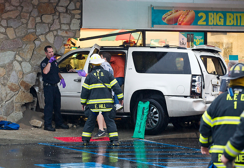 Firefighters and first responders arrive on-scene at about 6:15 pm Friday at a multi-car crash on rain-slicked Rt. 71 that ended with a Chevy Suburban careening through the front wall and windows of the 7-11 convenience store. The driver of the SUV was extricated by Manasquan firefighters and transported to the hospital.   6/7/13  photo by Andrew Mills