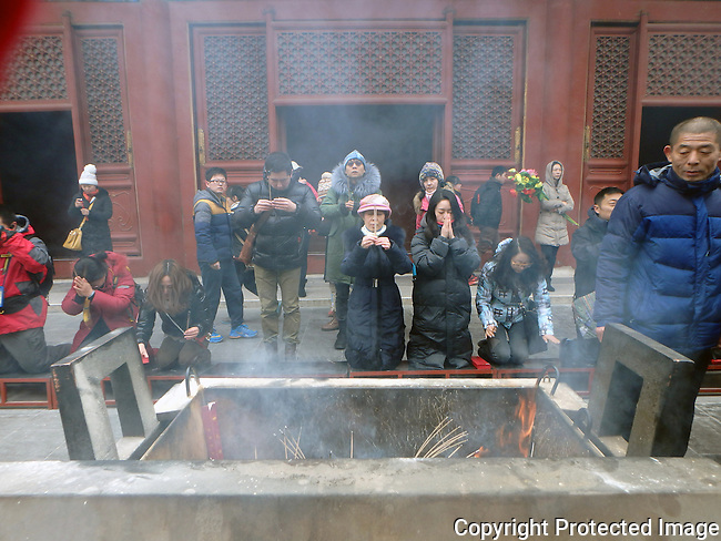 smoke rises from burning incense in a stone vat as people pray to their Buddhist gods at Lama Temple in Beijing at lunar new year