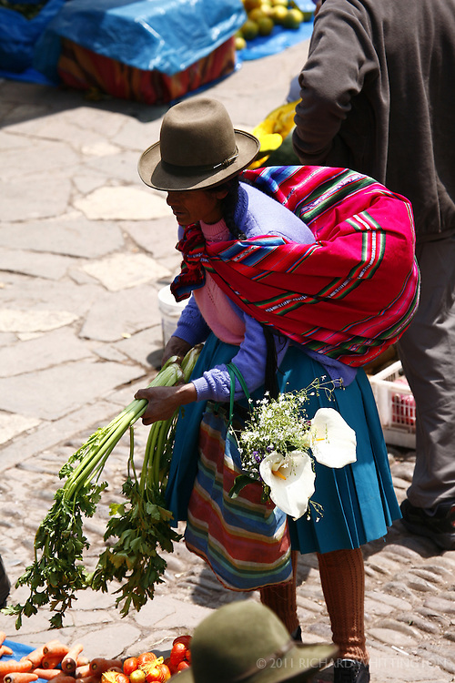 A Peruvian woman bargains with the vendor at the Pisac market.