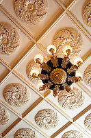 The view from below of an ornate plasterwork ceiling and gilded chandelier.