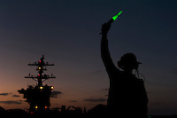 110205-N-7981E-121 ARABIAN SEA (Feb. 5, 2011) A Sailor assigned to Air Department, V-2 Division, signals while readying the bow catapults for an evening of flight operations on the flight deck of the Nimitz-class aircraft carrier USS Carl Vinson (CVN 70). The Carl Vinson Carrier Strike Group is deployed supporting maritime security operations and theater security cooperation efforts in the U.S. 5th Fleet area of responsibility. (U.S. Navy photo by Mass Communication Specialist 2nd Class James R. Evans / RELEASED)