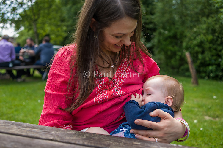 A mother breastfeeding her baby in a pub garden.<br /> <br /> Hampshire, England, UK<br /> 19/06/2013<br /> <br /> &copy; Paul Carter / wdiip.co.uk