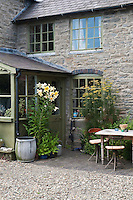 The front door of the restored stone-built Victorian farmhouse is accessed via a glassed-in slate-roofed porch