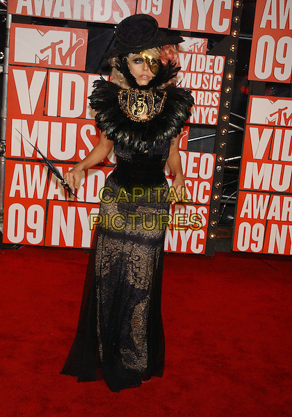 LADY GAGA (Joanne Stefani Germanotta).2009 MTV Video Music Awards arrivals held at Radio City Music Hall, New York, NY, USA..September 13th, 2009.full length black hat feathers gold beads beaded mask lace dress corset .CAP/ADM/MJ.©Michael Jade/AdMedia/Capital Pictures.