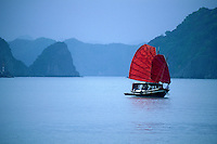 Traditional Vietnamese Junk with red sails flying, Halong Bay, Vietnam