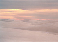 Sunset at White Sands National Monument.  As the sun set behind high, thin clouds, the white sands began reflecting the pink and salmon tones in the sky.  Using my longest telephoto lens, I was able to isolate a graphic composition of the dunes.<br /> <br /> Canon EOS 630, Canon 80-200 lens, Kodak Royal Gold 400 film