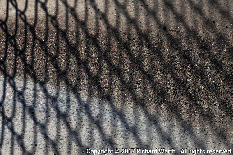 A chain link fence provides a thin veil, only slightly hiding rough concrete of the sidewalk outside a neighborhood elementary school.