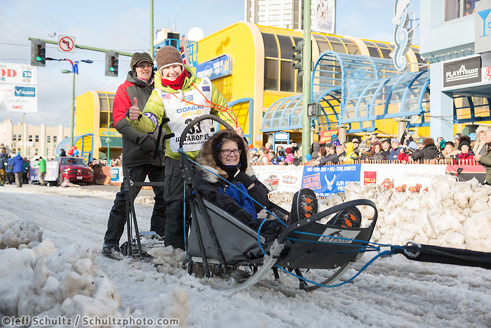 Yvonne Dabakk and team leave the ceremonial start line with an Iditarider at 4th Avenue and D street in downtown Anchorage, Alaska during the 2015 Iditarod race. Photo by Jim Kohl/IditarodPhotos.com