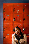 A teacher sits against lockers in the hallway of a school.