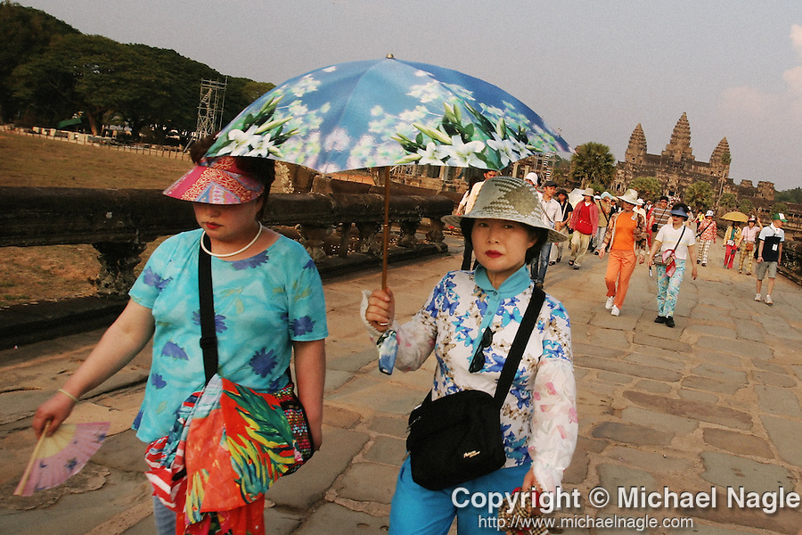 CAMBODIA  -  APRIL 7, 2005:  Chinese tourists dressed in floral patterns carry an floral print umbrella for shade from the sun after visiting Angkor Wat in Siem Reap on April 7th, 2005 in Cambodia.  (PHOTOGRAPH BY MICHAEL NAGLE)