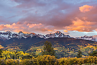 Uncompahgre National Forest, Colorado: Sunrise over Mount Sneffels and San Juan Range with hills of fall colored aspens and pines in the valley of East Dallas Creek