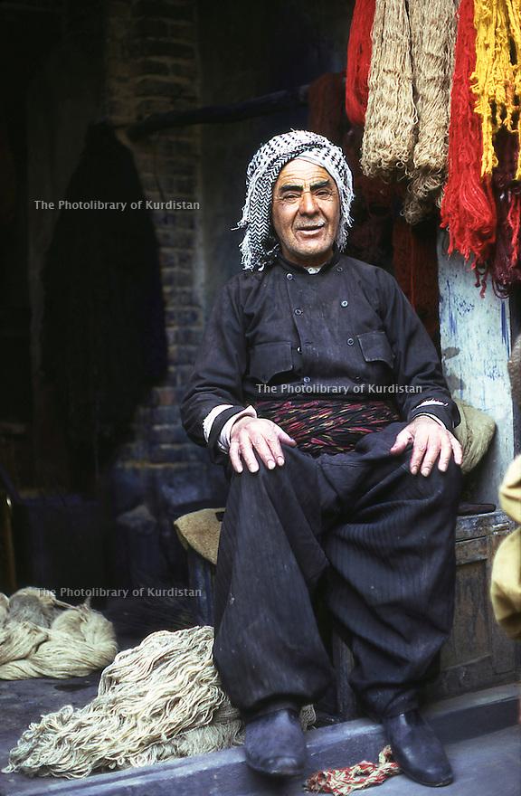 Iran 1975.Mahabad: Man in his shop selling wool