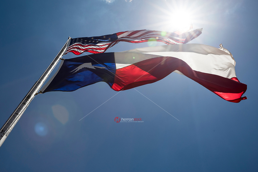 Unique view from below of the U.S. and Texas flags on a flag pole waving in the gentle breeze of the Lone Star State.