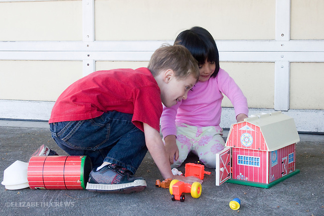 Berkeley CA Two four-year-olds involved in imaginative cooperative play with farm toys  MR