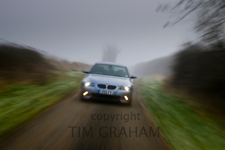 BMW 5-series car drives along empty country road in adverse foggy weather, Oxfordshire,  England, United Kingdom