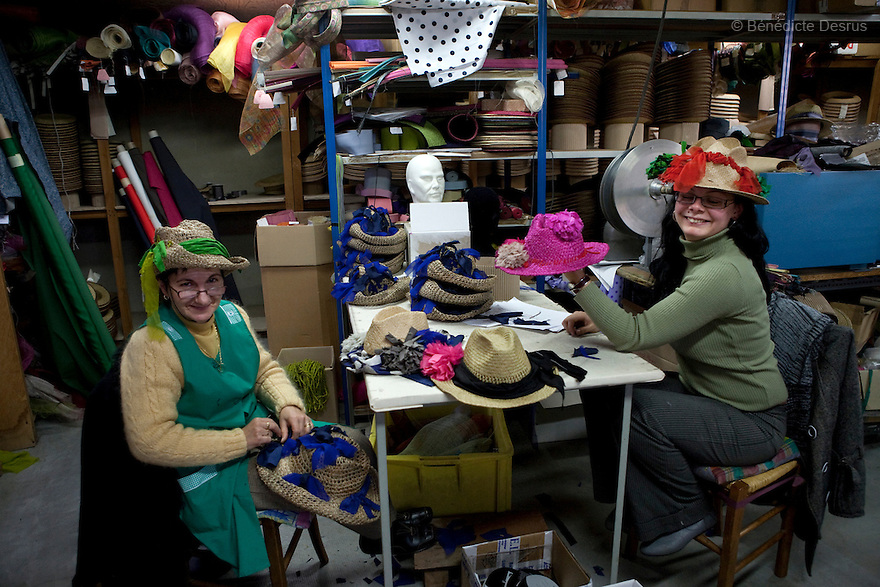 9 december 2009 - Coustilleres' hat factory, Septfonds, France - Severine Dhotel and Nicole Pajot, workers, wear the Lanvin Haute couture's hats at the Coustilleres' hat factory..Septfonds is the heart of French straw hat making, due to its very ancient hatter tradition. The hat making industry had its commercial peak in the late 19th century..Coustillères is a family owned hat making factory that has been making straw hats in Septfonds for nearly 100 years. They make hats from straw, felt, and cloth as well as caps. The current owner is Jean-Claude Coustilleres. He is one of the last hat makers of the region..The straw hat making process is very labor intensive and numerous hands are involved. Nearly all of the equipment is over 100 years old, they use the original presses and tools including aluminium molds and sewing machines and dye their own straw continuing the traditional methods of manufacturing. The hat blocking and shaping, straw braids construction and dyeing are all done by hand..The company works on behalf of fashion houses and makes a variety of regional and historical hats. It produces 2 collections a year distributed by a network of salespeople and through a catalog to clients around the world. Photo credit: Benedicte Desrus