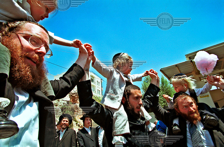 Orthodox Jewish men dance with their three year old sons before they receive their first haircut in the Chalakeh ceremony.  This Chalakeh is being performed at the Shimon Hatzadik tomb in the east Jerusalem Palestinian neighbourhood of Sheikh Jarach..