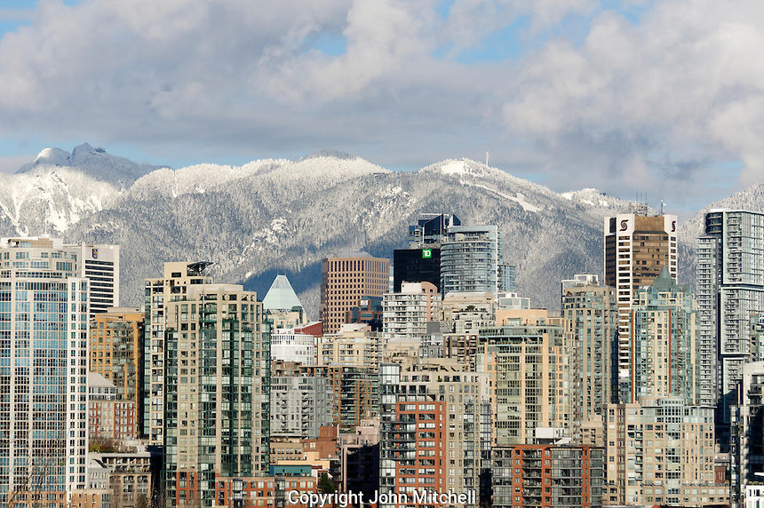 Skyline of downtown Vancouver in winter with snow covered North Shore Mountains, British Columbia, Canada